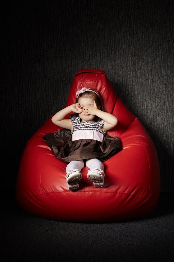 小女孩坐红色装豆子小布袋 图库摄影