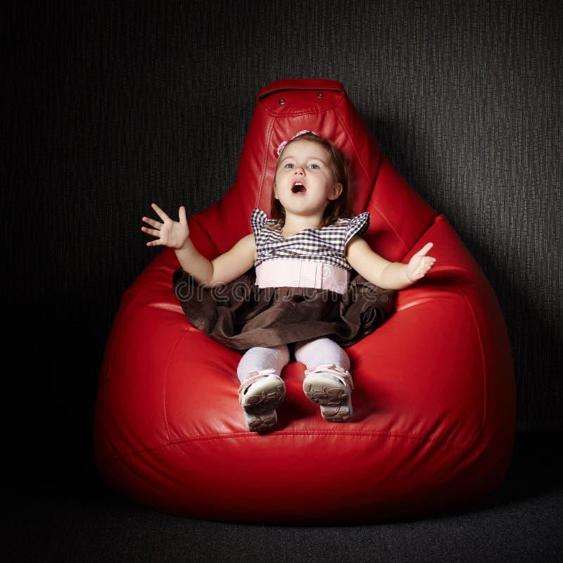小女孩坐红色装豆子小布袋 免版税库存图片