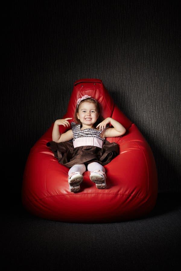 小女孩坐红色装豆子小布袋 免版税库存照片