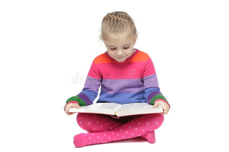 小女孩坐读书的楼层 免版税库存照片