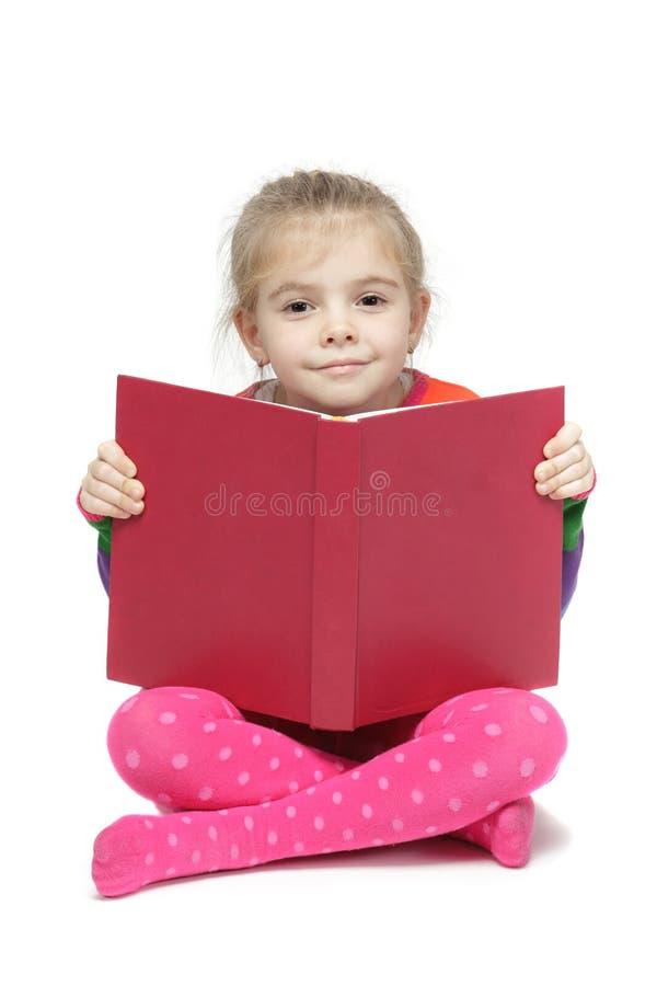 小女孩坐读书的楼层 库存图片