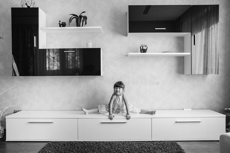 小女孩坐麻线在家具分裂了 通过pa 免版税库存图片