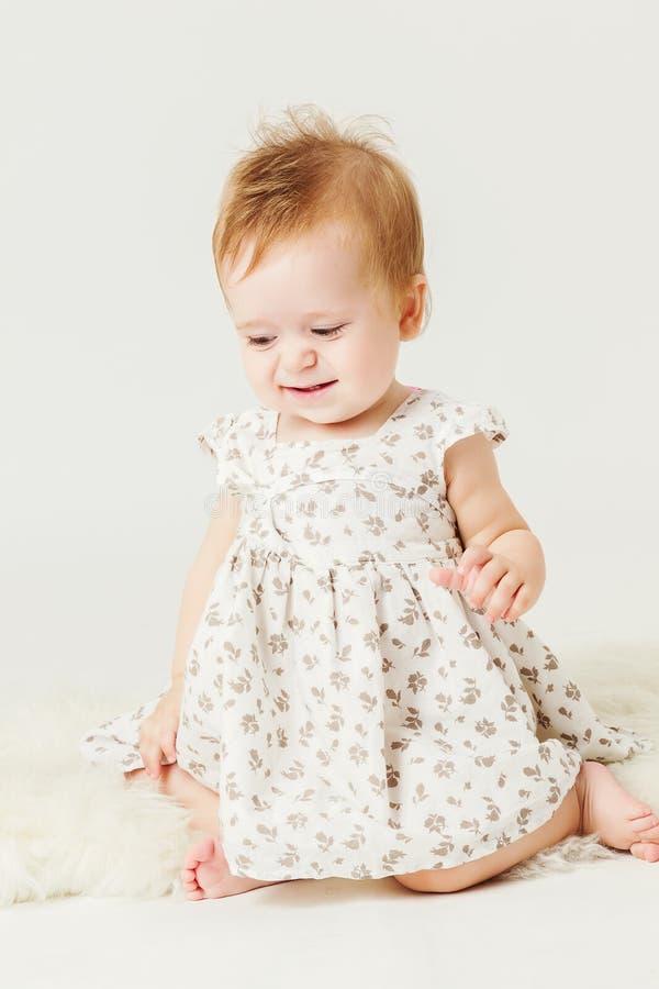 小女孩坐绵羊的衣物 库存图片