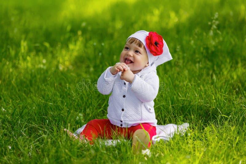 小女孩坐绿草 免版税库存图片
