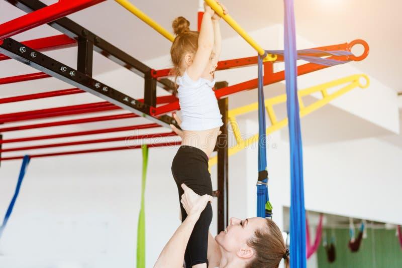小女孩垂悬在标志横线的,妈妈支持 免版税库存照片