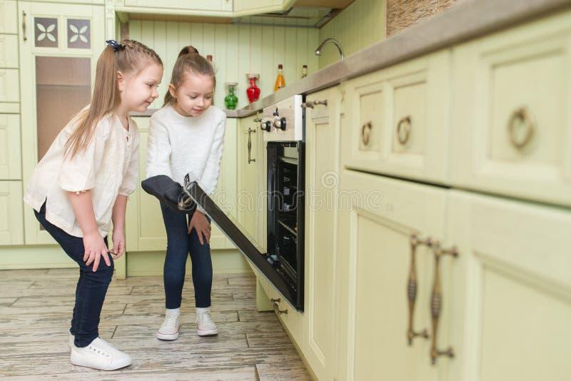 小女孩姐妹看在烤箱的鲜美曲奇饼 免版税库存照片