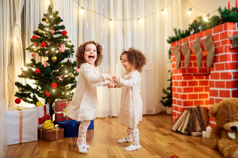 小女孩孪生儿童圣诞节跳舞,获得乐趣,笑 免版税库存图片