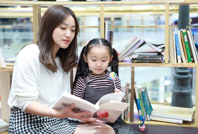 小女孩实践读书在精采地被阐明的市场上 图库摄影