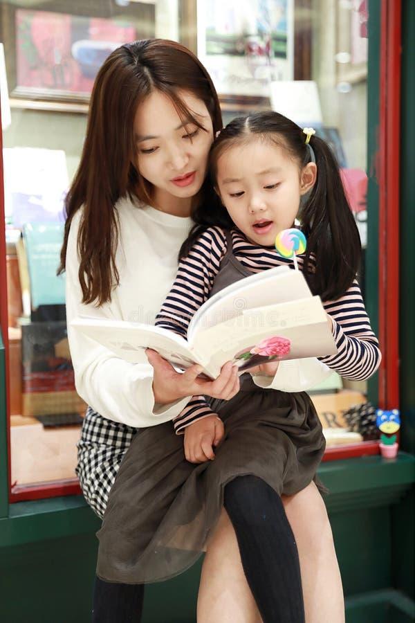 小女孩实践读书在精采地被阐明的市场上 免版税库存图片