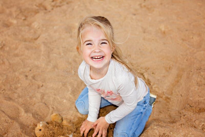 小女孩小女孩坐在海滩和gri的沙子 库存照片