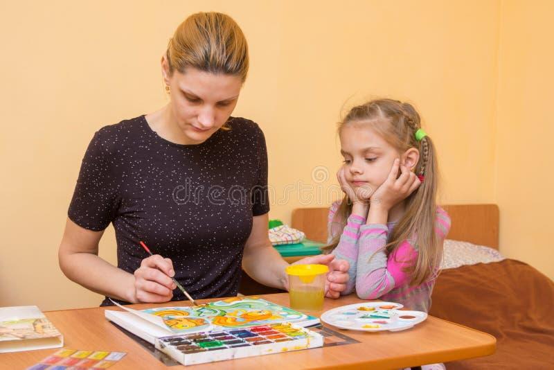 小女孩小心地注意显示如何绘水彩的老师 库存照片