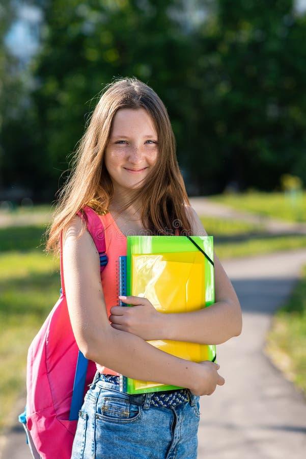 小女孩少年 在夏天在城市 在他的手上他拿着文件夹和笔记本 愉快地情感地微笑 库存图片