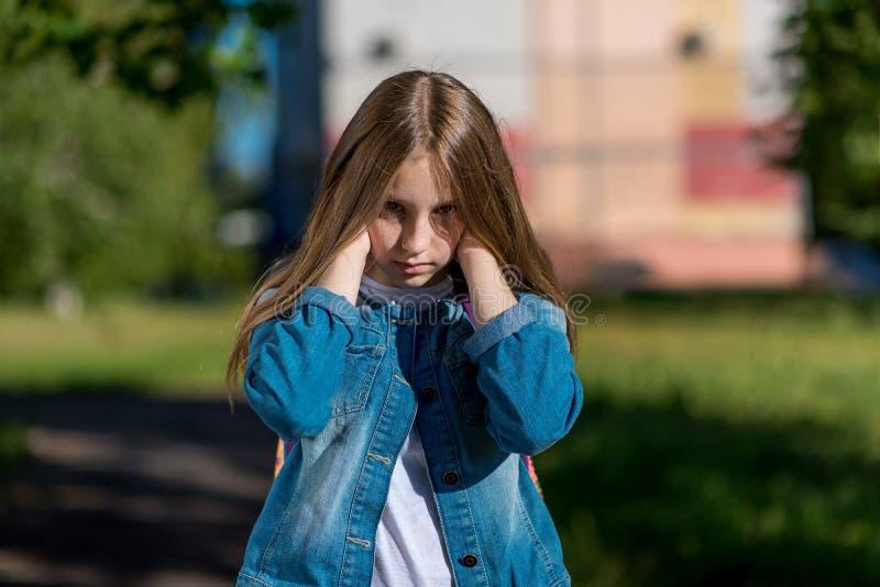 小女孩少年 在夏天城市 有棕榈的接近的耳朵您的手 喧闹声,强的尖叫的概念 库存图片