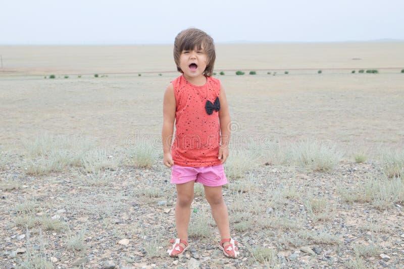 小女孩尖叫在大风景环境里 响亮地情感地说的孩子,唱与表示的一首歌曲 免版税库存图片