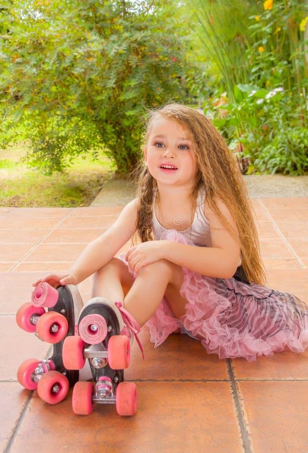 小女孩幼儿园坐佩带她的溜冰鞋和盘她的腿,在庭院背景