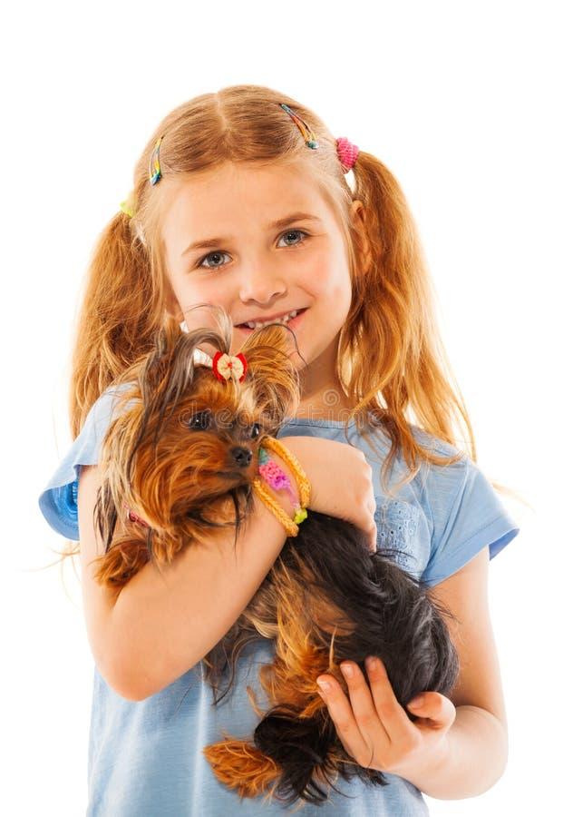 小女孩微笑和举行逗人喜爱的小狗 图库摄影