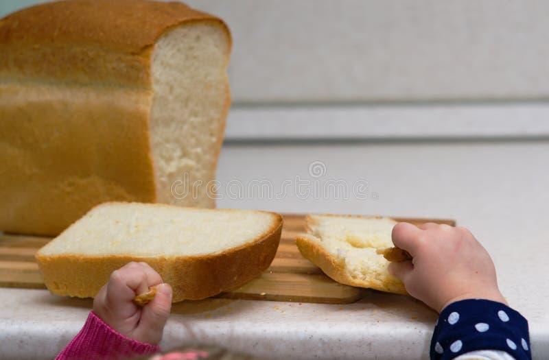小女孩打破在特写镜头桌上的面包 库存图片