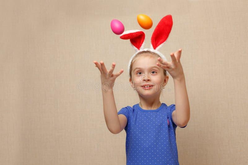 小女孩投掷一些个复活节彩蛋 免版税库存照片
