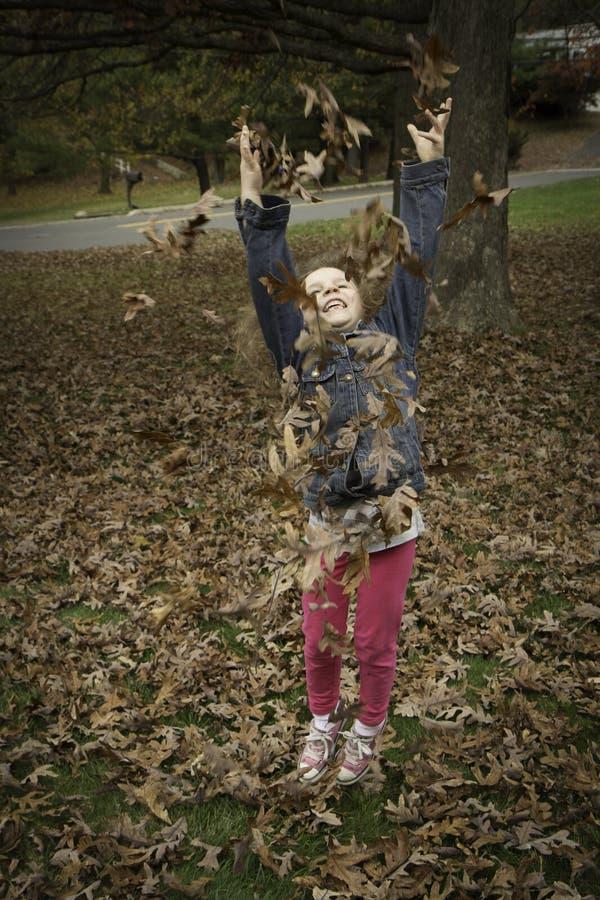 小女孩投掷叶子 免版税图库摄影