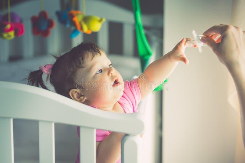 小女孩拉扯她的手对钝汉,站立在婴孩小儿床 被定调子的图片 免版税库存图片