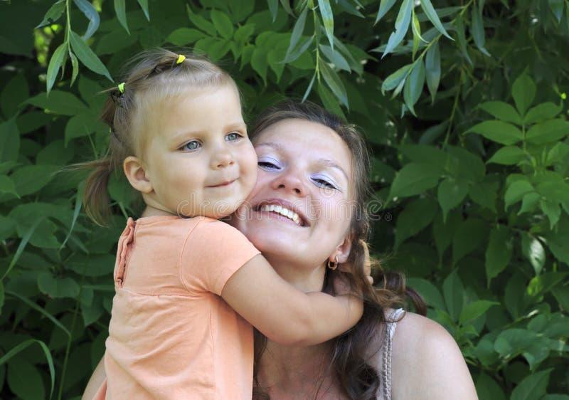 小女孩拥抱他的母亲。 免版税库存图片
