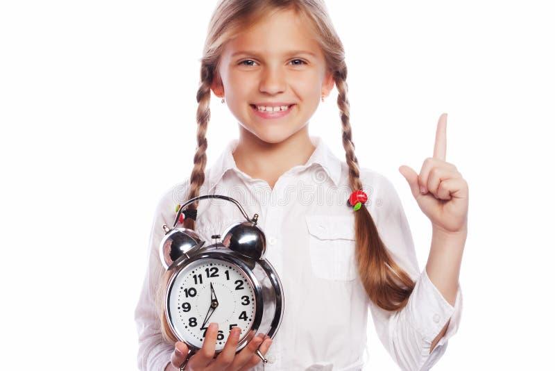 小女孩拿着时钟,当指向与她的索引f时 免版税库存照片