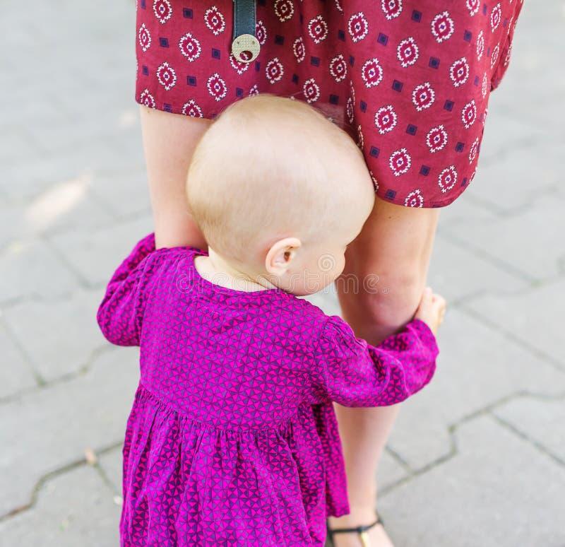小女孩接受mother& x27; s腿 免版税图库摄影