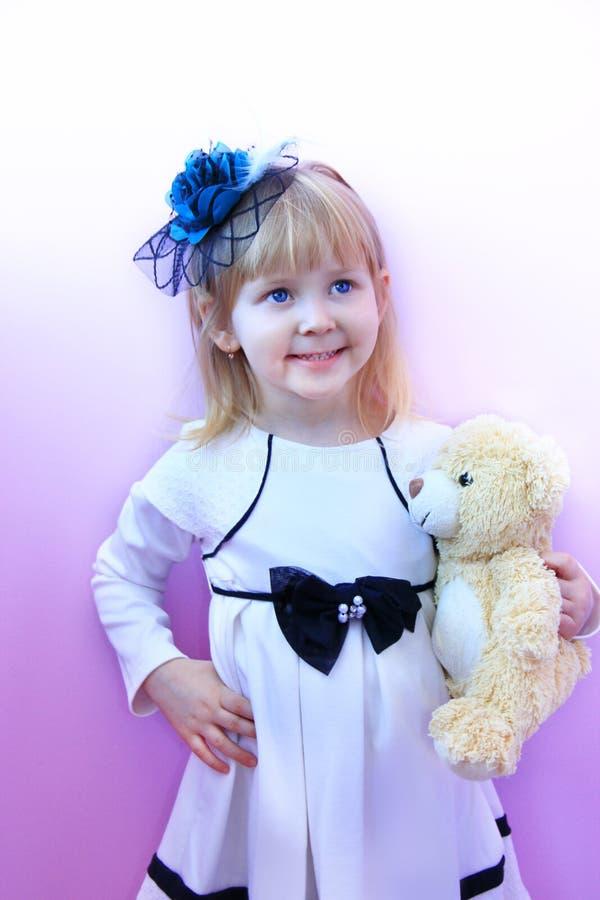 小女孩时兴的帽子的和有玩具在手上微笑和摆在淡紫色背景的小熊的 图库摄影