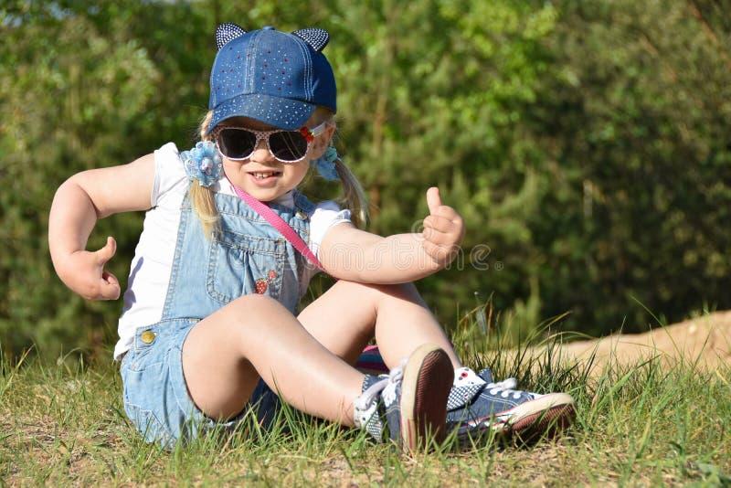 小女孩是使用和笑在绿色草坪在夏天 库存照片