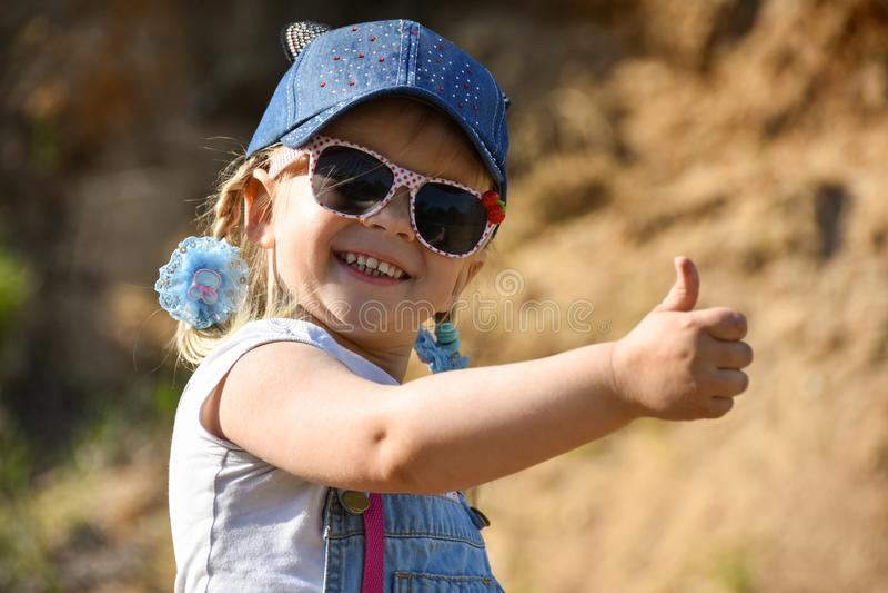 小女孩是使用和笑在绿色草坪在夏天 图库摄影