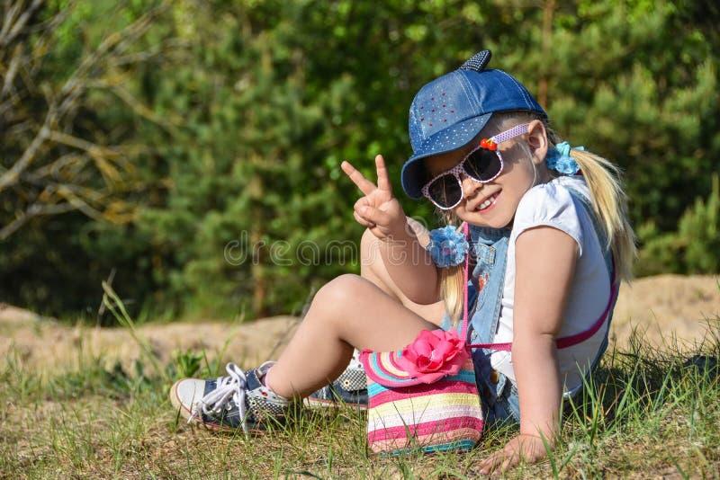 小女孩是使用和笑在绿色草坪在夏天 免版税库存照片