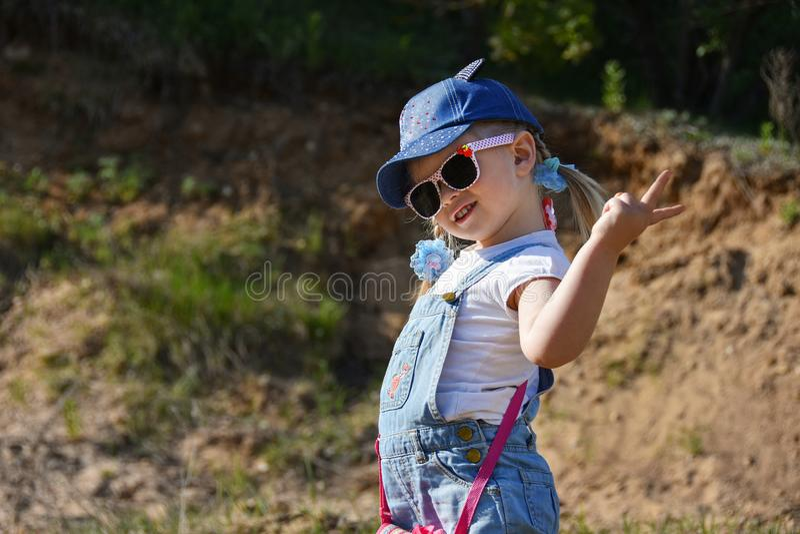 小女孩是使用和笑在绿色草坪在夏天 免版税库存图片
