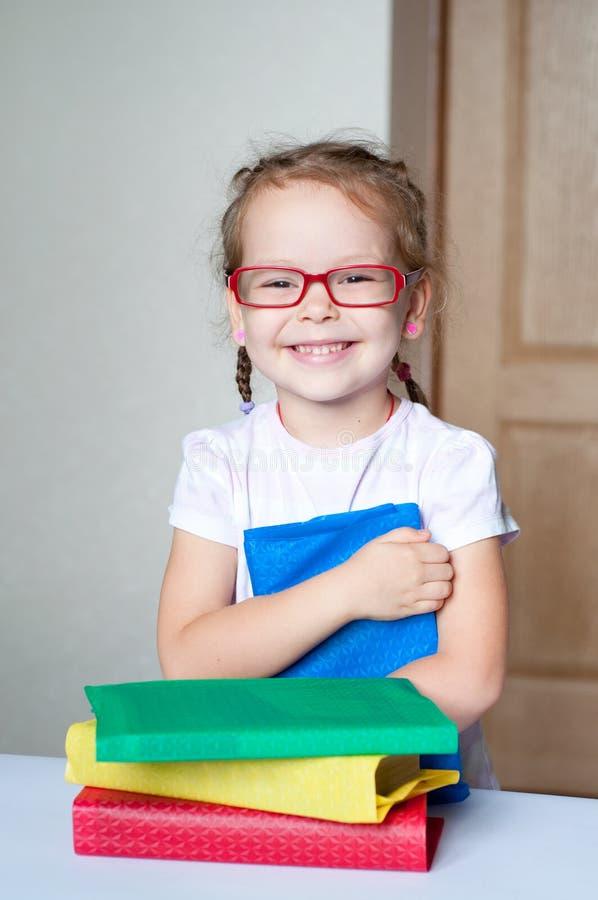 小女孩是阅读书佩带的玻璃 库存图片