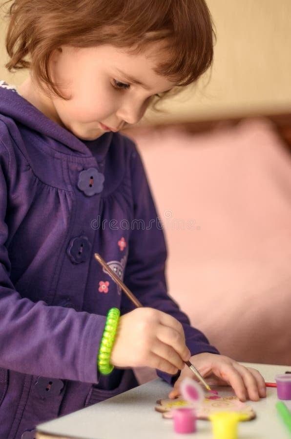 小女孩有油漆刷的绘画玩具在家 免版税库存照片