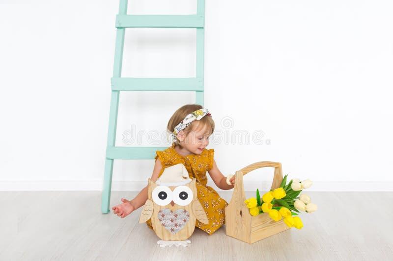 小女孩有郁金香的和有玩具猫头鹰的在有梯子的轻的春天演播室坐 免版税库存图片
