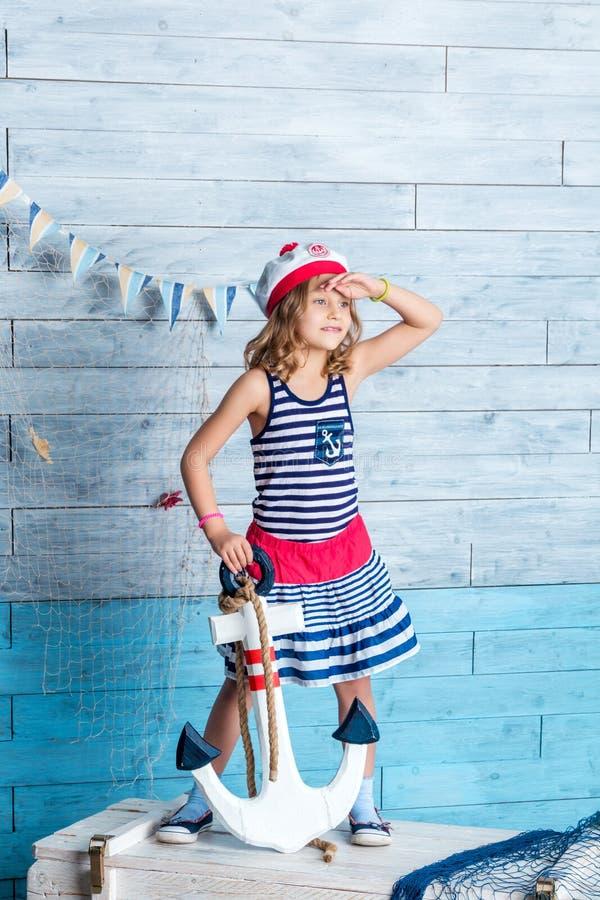 小女孩水手身分和保留船锚 免版税库存图片