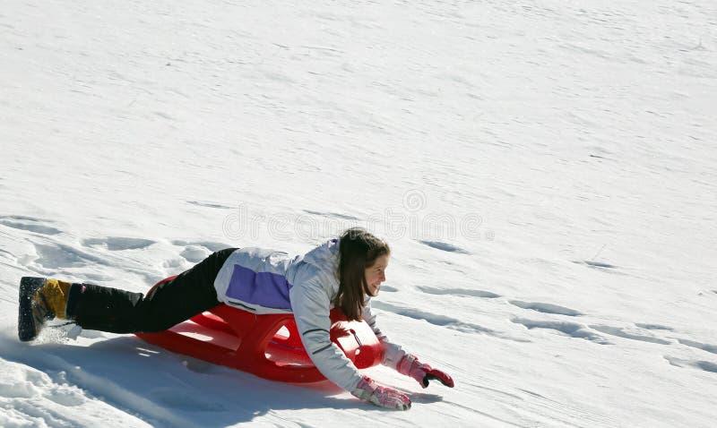 小女孩沿着走说谎在雪撬 免版税库存照片