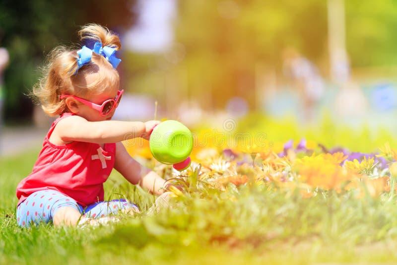 小女孩浇灌的花在夏天 免版税库存照片