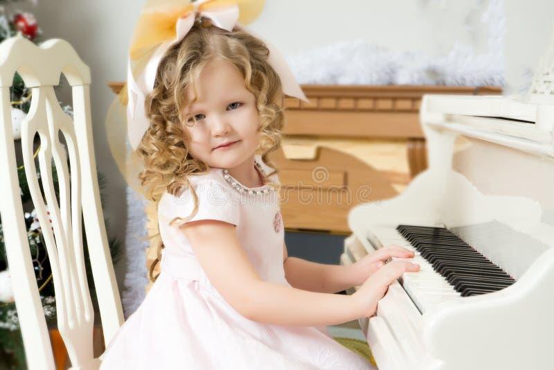 小女孩演奏在钢琴的音乐 免版税库存图片