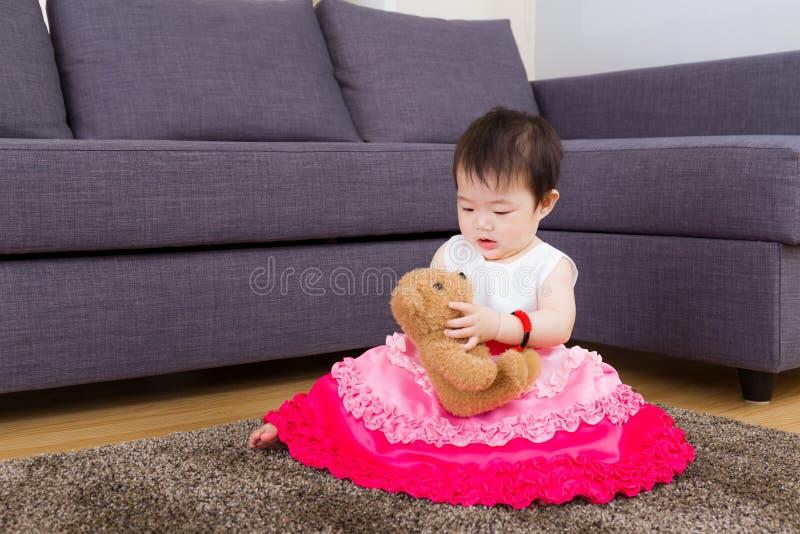 小女孩演奏玩偶和坐地毯 免版税库存照片