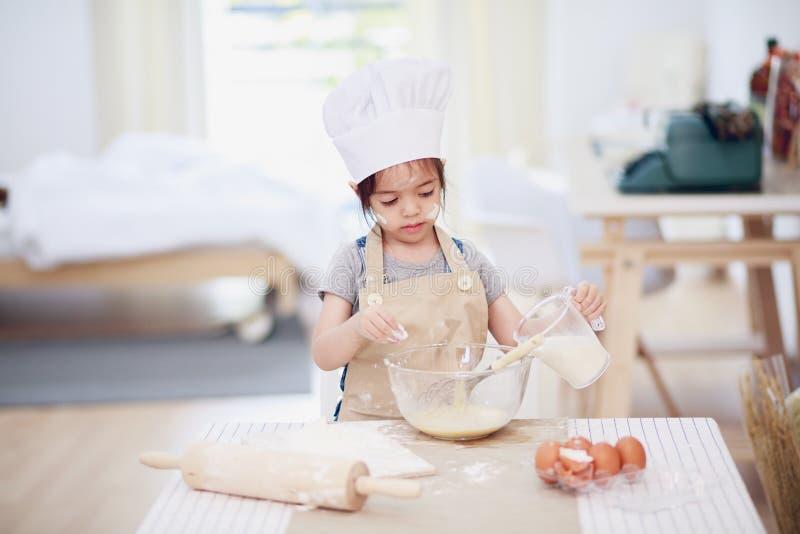 小女孩烘烤在厨房里 免版税库存照片