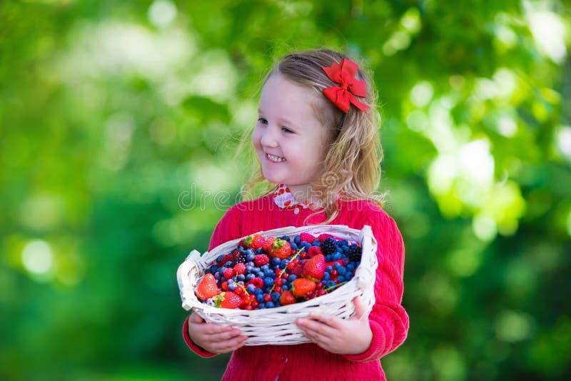 小女孩用在篮子的新鲜的莓果 免版税库存照片