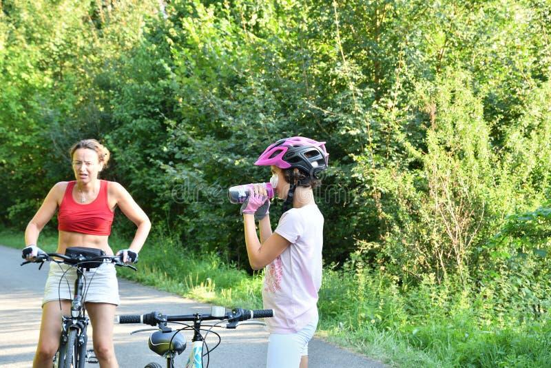 小女孩用在骑自行车在路的家庭的水刷新 免版税库存图片