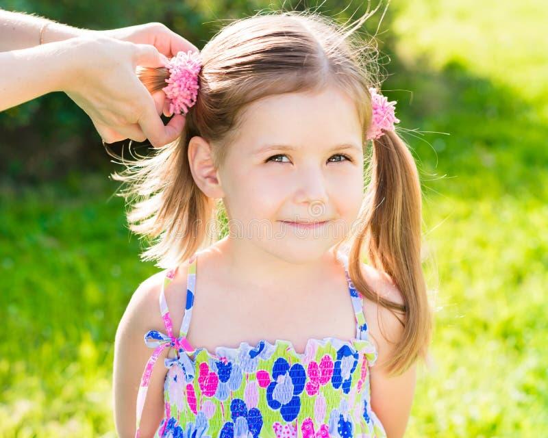 小女孩用她的做发型的妈妈的手 库存图片