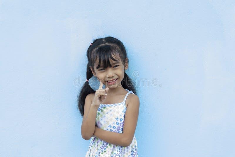 小女孩用手指微笑着指着脸颊 库存照片