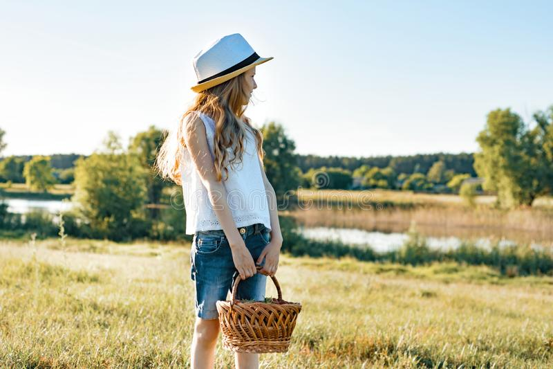 小女孩用篮子草莓,草帽室外夏天画象  自然背景,农村风景,绿色草甸, 免版税库存图片