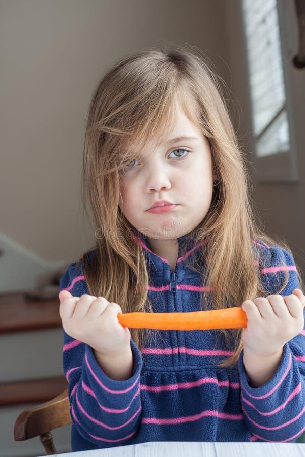 小女孩用红萝卜 库存图片