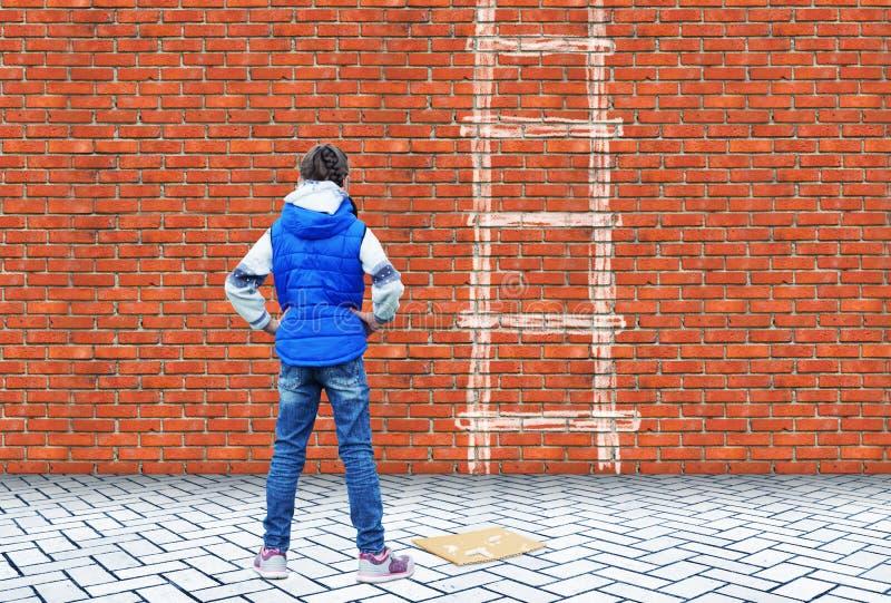 小女孩画了与在砖墙上的白垩克服这墙壁的梯子 图库摄影