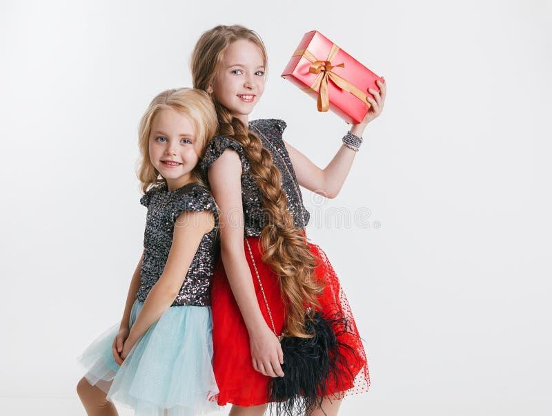 小女孩画象有站立在礼服的节日晚会的卷曲发型的有衣服饰物之小金属片的,拿着礼物 库存照片