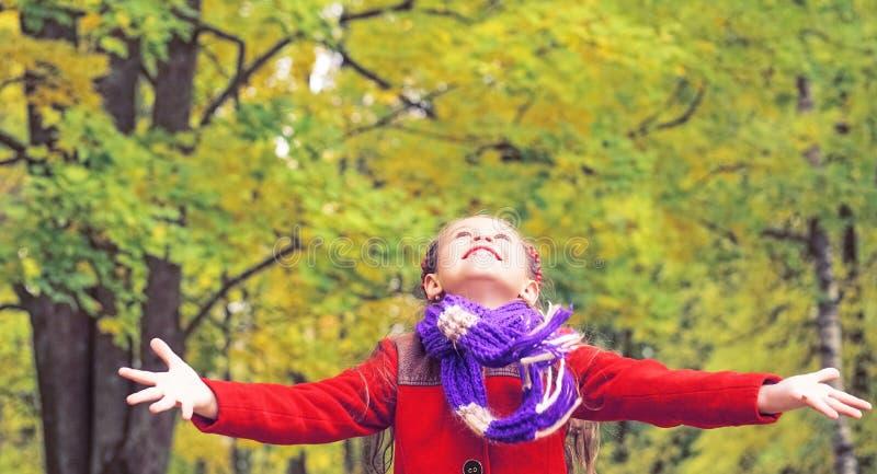 小女孩画象有胳膊的在秋天公园伸出户外 免版税图库摄影